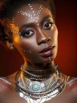 Beautiful afro girl with drawings on skin and metal accessories. Beauty shot on red background. Copy space.